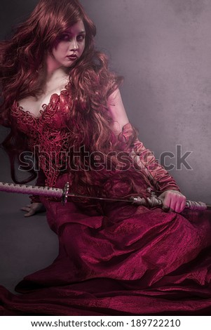 beautiful woman dressed in red satin dress and samurai sword - stock photo
