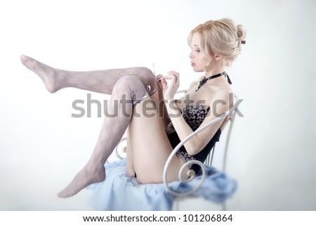 beautiful woman dresses stockings on feet - stock photo