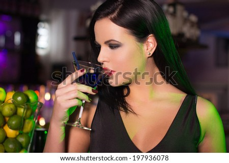 Beautiful woman drink cocktail in bar at night - stock photo