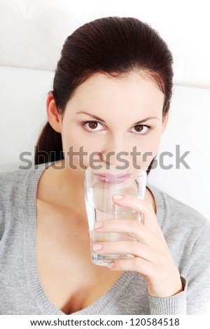 Beautiful woman drinking a clean mineral water from glass . - stock photo
