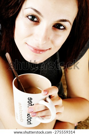 Beautiful woman drinking a cup of coffee - stock photo