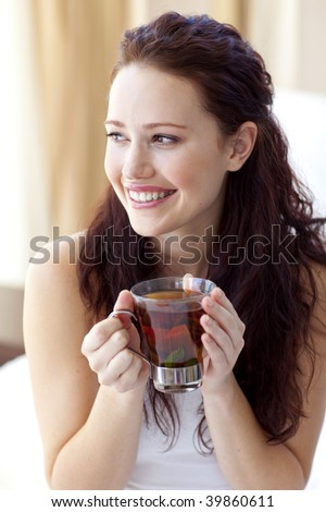 Beautiful woman drinking a cup of tea in bed in the morning