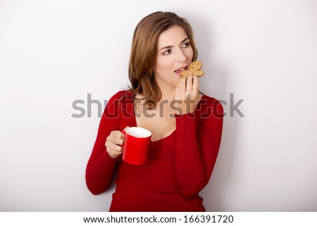 Beautiful woman drinking a hot coffee and eating a gingerbread cookie, against a gray wall - stock photo