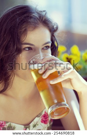 Beautiful woman drinking beer outside in the summer. - stock photo