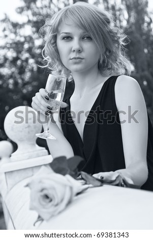 Beautiful woman drinking champagne from wineglass in black and white with soft blue tint