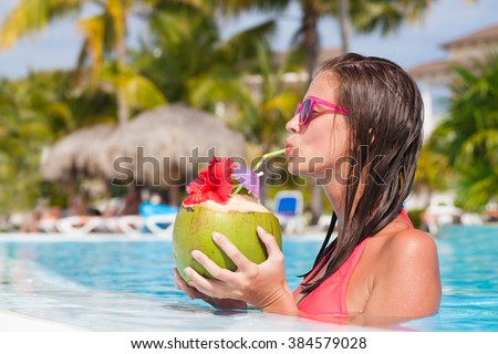 beautiful woman drinking coconut by the pool - stock photo