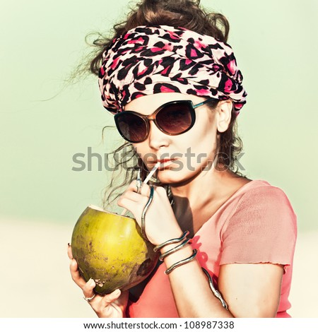 Beautiful woman drinking coconut outdoor - stock photo