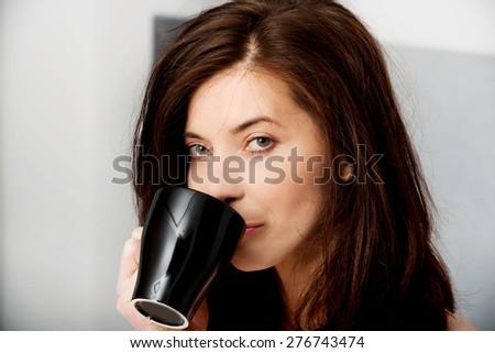 Beautiful woman drinking coffee in bed. - stock photo