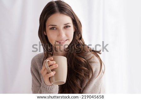 beautiful woman drinking coffee in the morning sitting by the window - stock photo