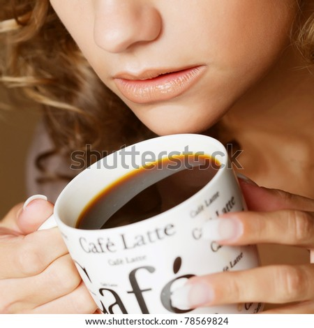 Beautiful woman drinking coffee. studio shot. - stock photo