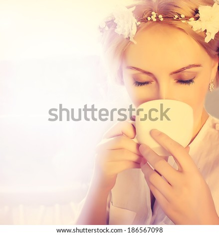 beautiful woman drinking coffee. woman with a coffee cup at window - stock photo