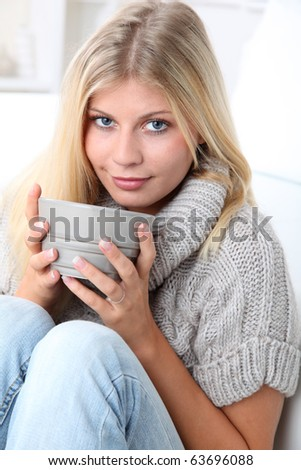 Beautiful woman drinking hot drink in winter - stock photo