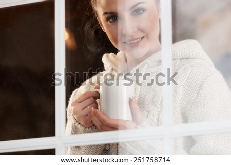 Beautiful woman drinking hot drink standing by the window. View from outside. - stock photo
