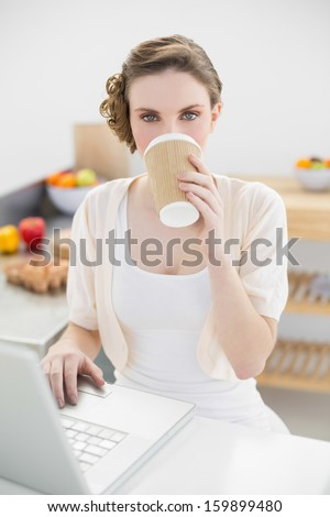Beautiful woman drinking of disposable cup using her notebook in kitchen at home - stock photo
