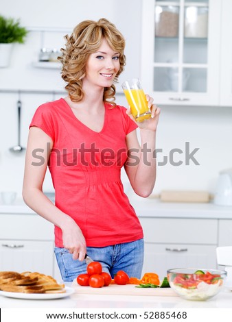 Beautiful woman drinking orange juice and cooking in the kitchen - indoors - stock photo