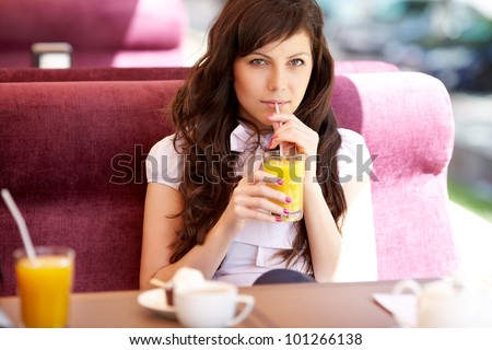 beautiful woman drinking orange juice sitting in a cafe