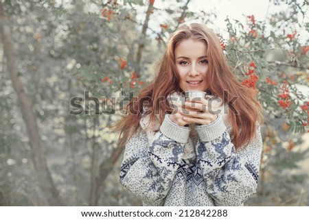 beautiful woman drinking tea from thermos in the forest - stock photo