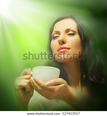 Beautiful woman drinking tea on green blurred background