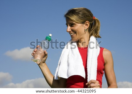 Beautiful woman drinking water after fitness - stock photo