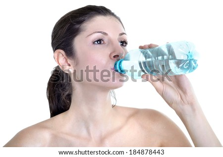 Beautiful woman drinking water after gymnastic exercises