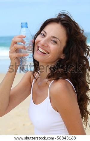 Beautiful woman drinking water at the beach - stock photo