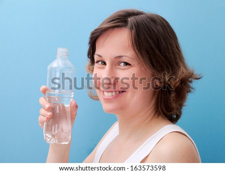 Beautiful woman drinking water from a bottle - stock photo