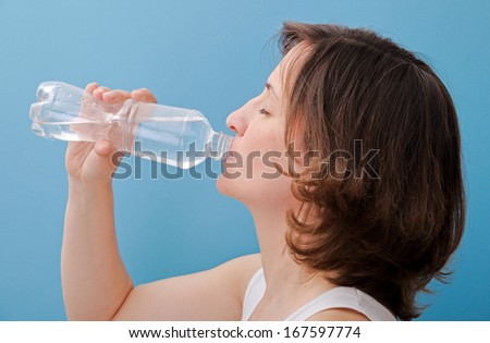 Beautiful woman drinking water from a bottle