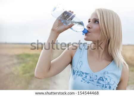 Beautiful woman drinking water from bottle while standing on field - stock photo