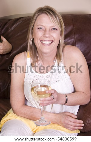 Beautiful Woman Drinking Wine at Home on the Couch