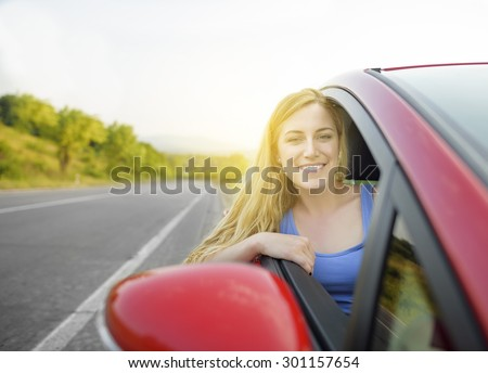 Beautiful woman driving a car on a country road. Concept travel.