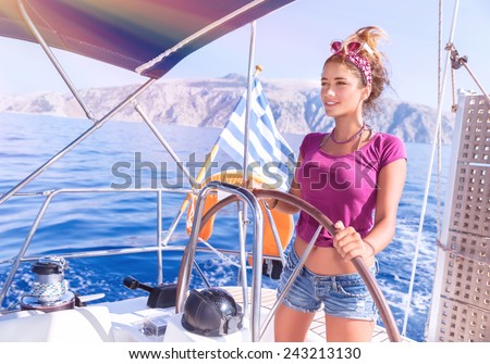 Beautiful woman driving sailboat, sexy young captain standing behind helm and enjoying bright sun light, active lifestyle, summer vacation concept  - stock photo