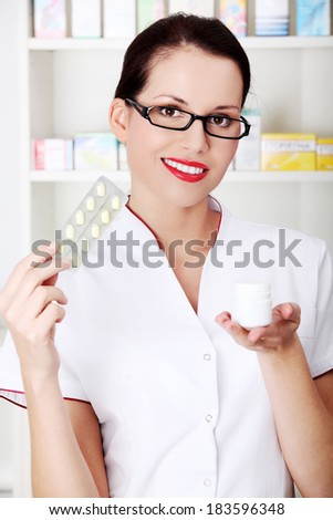 Beautiful woman druggist is holding some tablets.Health care concept. - stock photo