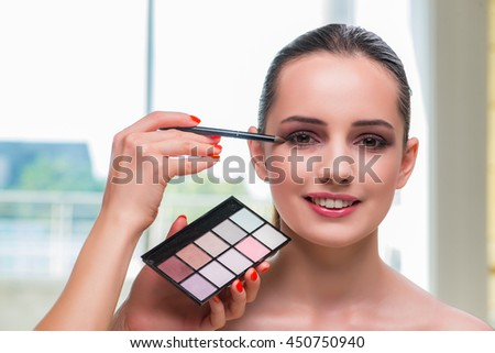 Beautiful woman during make-up cosmetics session - stock photo