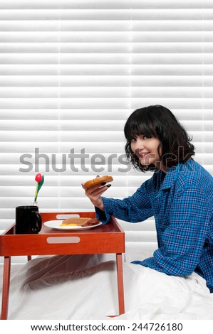Beautiful woman eating a big breakfast in bed - stock photo