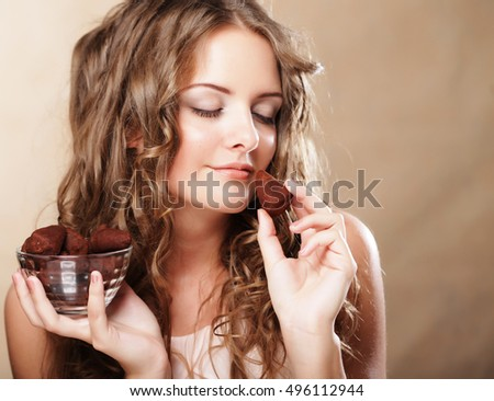 Beautiful woman eating a chocolate bonbon