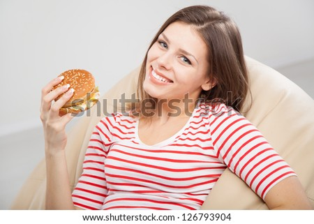 Beautiful woman eating a hamburger - stock photo