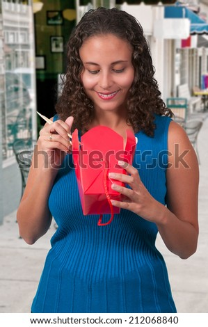 Beautiful woman eating Asian takeout food (photo illustration / image composite) - stock photo