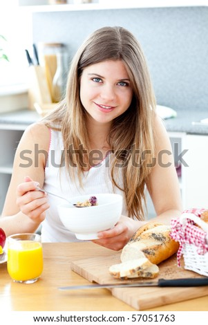 Beautiful woman eating breakfast in her kitchen