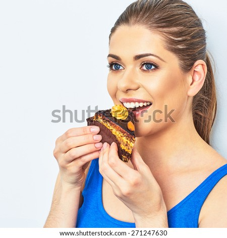 Beautiful woman eating cake. Studio portrait. Young female model.