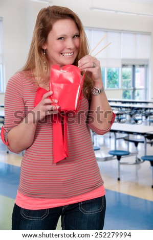 Beautiful woman eating Chinese Japanese or Asian takeout food - stock photo