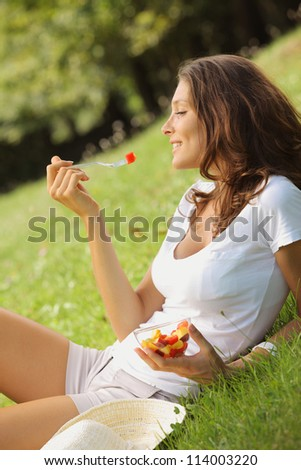 Beautiful woman eating fruit salad on a lawn - stock photo
