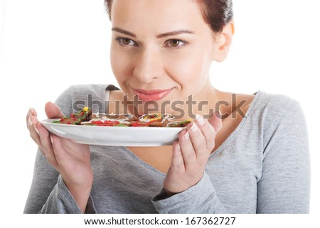 Beautiful woman eating gingerbread cookies. On white background.