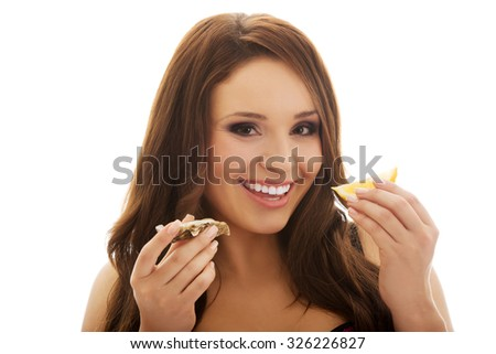 Beautiful woman eating raw oyster with organic lemon.