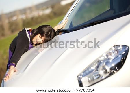 Beautiful woman embracing her new car - stock photo