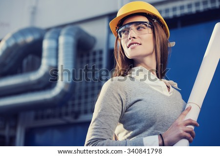 beautiful woman engineer is standing in front of an industrial pipes background - stock photo