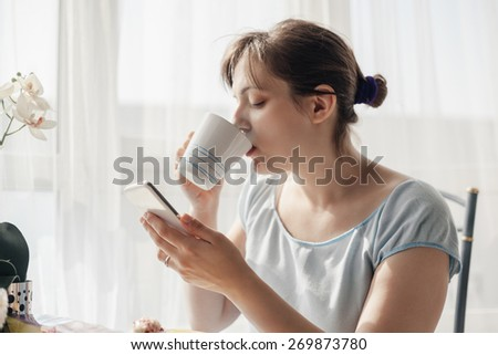 Beautiful Woman Enjoying A Cup Of Coffee At Home And Using Smart Phone - stock photo
