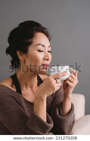 Beautiful woman enjoying a cup of tea or coffee - stock photo
