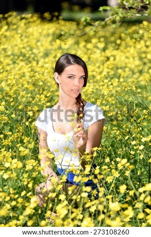 Beautiful woman enjoying daisy field, nice female lying down in the meadow of yellow flowers, pretty girl relaxing outdoor, holding plant, happy young lady and spring green nature, harmony concept - stock photo