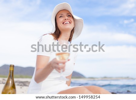 Beautiful woman enjoying glass of wine on the beach - stock photo
