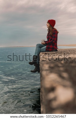 Beautiful woman enjoying her day in the lake with a mug of hot coffee